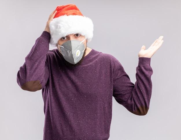 Giovane in maglione viola e cappello da babbo natale che indossa la maschera protettiva per il viso guardando la telecamera confusa con il braccio alzato in piedi su sfondo bianco