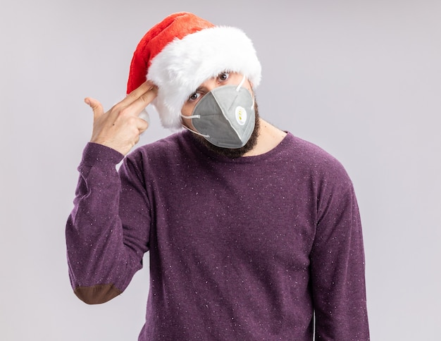Giovane uomo in maglione viola e cappello da babbo natale che indossa la maschera protettiva per il viso che fa il gesto della pistola con le dita sul tempio stanco e annoiato in piedi su sfondo bianco