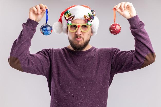 Giovane uomo in maglione viola e cappello da babbo natale indossando occhiali divertenti tenendo le palle di natale guardando la fotocamera confuso e dispiaciuto in piedi su sfondo bianco