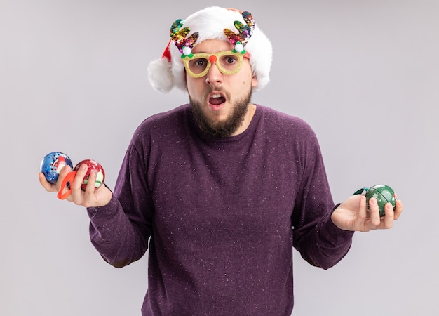 Young man in purple sweater and santa hat wearing funny glasses holding christmas balls looking at camera confused standing over white background
