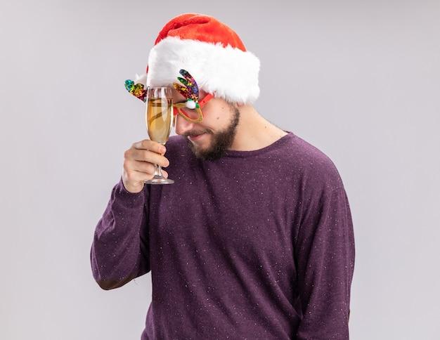 Giovane uomo in maglione viola e cappello da babbo natale indossando occhiali divertenti tenendo un bicchiere di champagne guardando stanco e annoiato in piedi su sfondo bianco