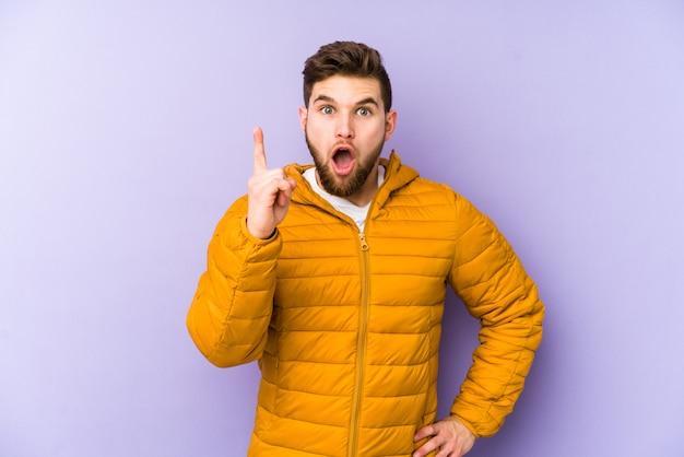 Young man on purple wall having an idea