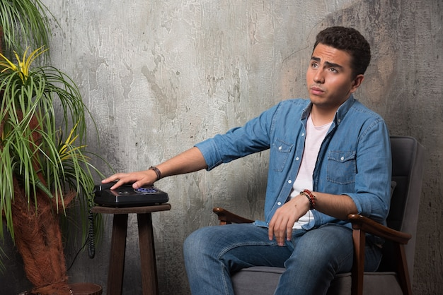 若い男は電話を置き、椅子に座った。高品質の写真