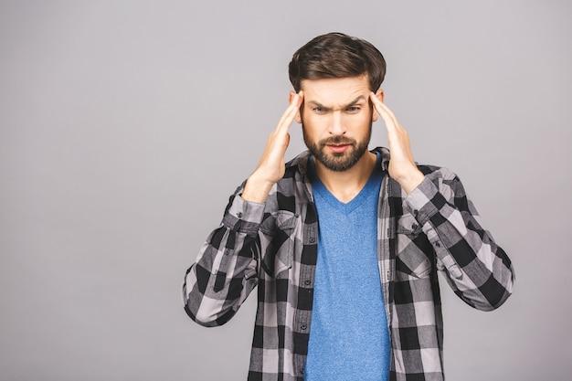 Молодой человек приложил руки к голове. он чувствует себя больным и болит голова из-за некоторых проблем. его стресс делает его неудобным и несчастным