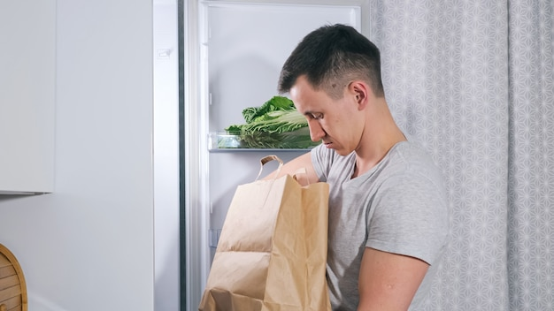 Young man puts different food products into large fridge