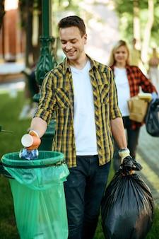 Молодой человек складывает мусор в полиэтиленовый пакет в парке, волонтерство
