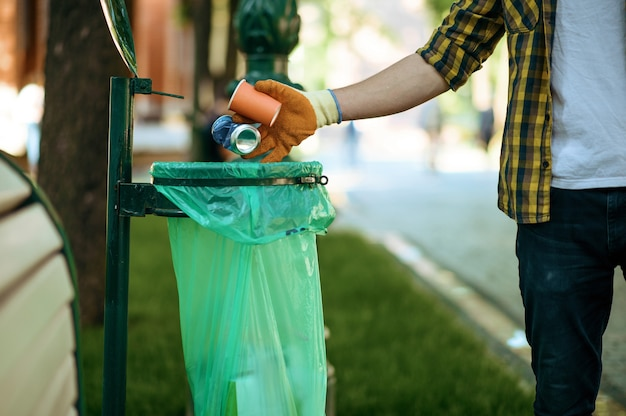 Young man puts garbage in plastic bag in park, volunteering. male person cleans forest, ecological restoration, eco lifestyle, trash collection and recycling, ecology care, environment cleaning