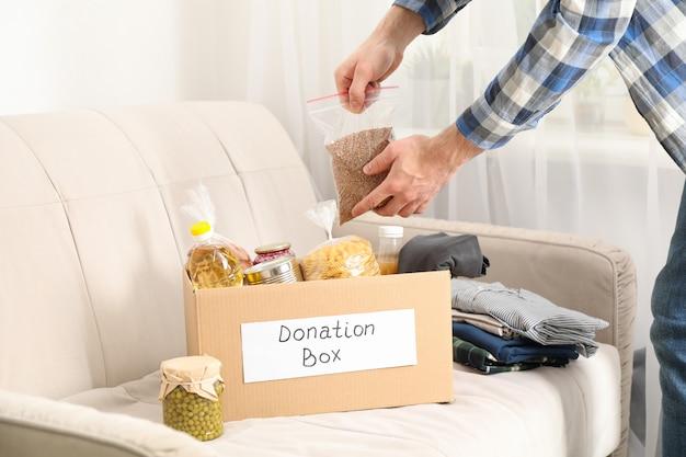 Молодой человек кладет продукты в ящик для пожертвований. доброволец