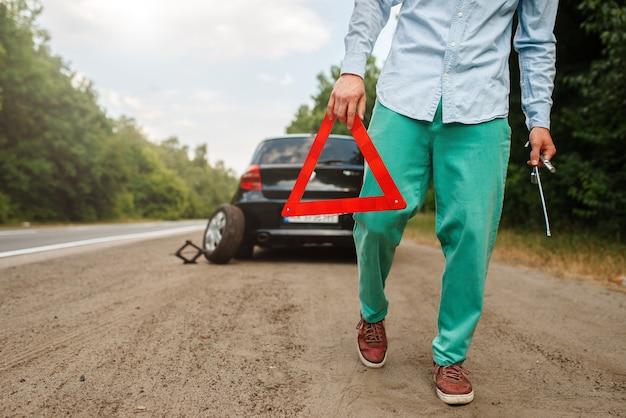 Молодой человек ставит на дорогу знак аварийной остановки, поломка автомобиля.