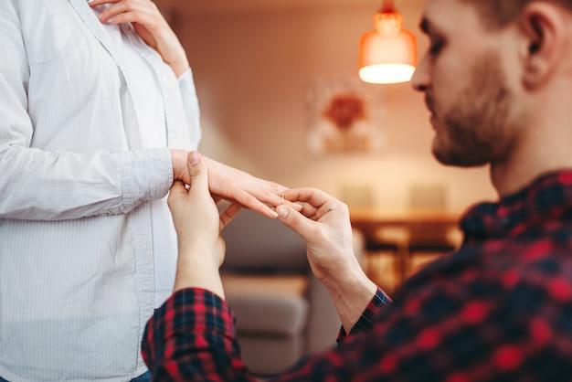 若い男は、最愛の人の指に結婚指輪を置きます。