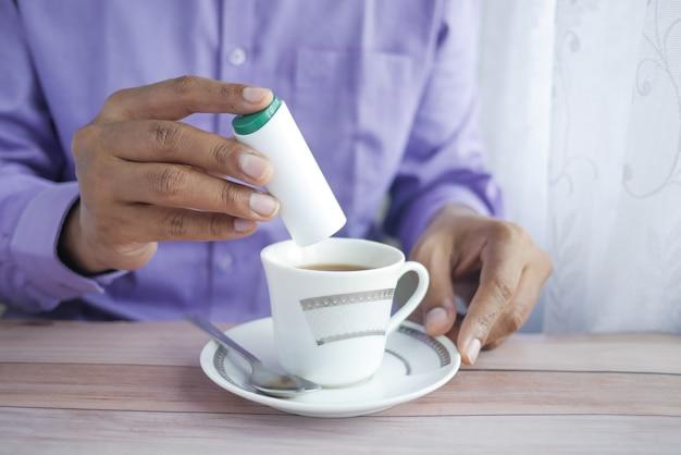 お茶に人工甘味料を入れる青年