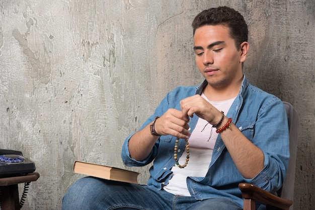 Young man putting on bracelet and sitting on chair with book on marble background. high quality photo