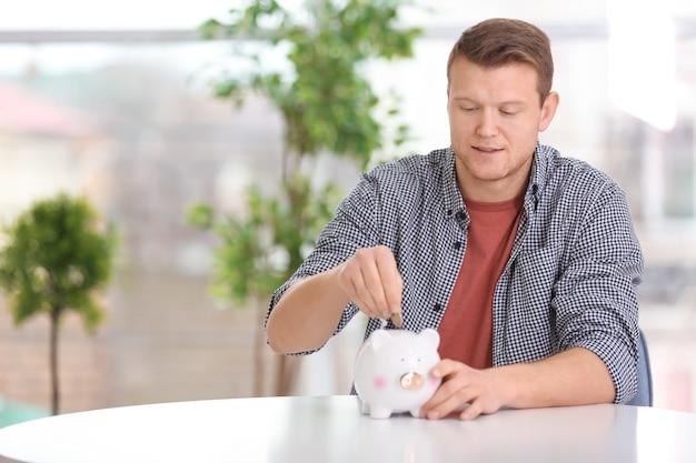 屋内のテーブルで貯金箱にコインを入れる若い男