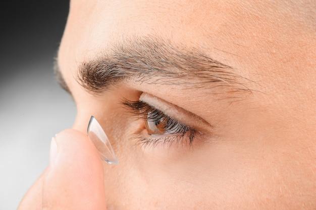 Молодой человек ставит контактные линзы, крупным планом