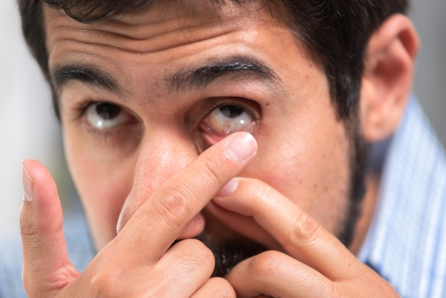 Young man putting contact lens in his left eye, close up