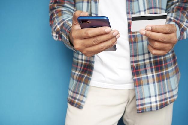 Молодой человек кладет детали кредитной карты на смартфон