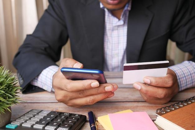 스마트 폰에 신용 카드 세부 정보를 넣어 젊은 남자