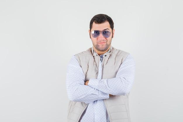 Giovane che indossa gli occhiali mentre in piedi con le braccia incrociate in giacca e berretto beige e sembra serio. vista frontale.
