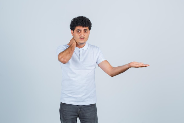 Young man putting hand on neck, having neck pain and stretching hand toward right  in white t-shirt and jeans and looking harried. front view.