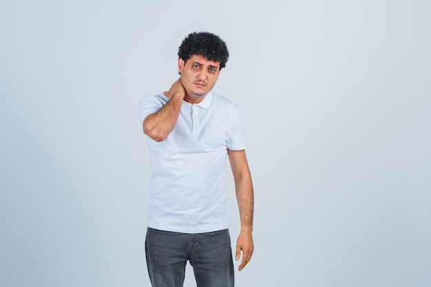 Young man putting hand on neck, having neck pain in white t-shirt and jeans and looking harried. front view.