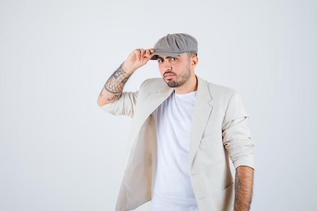 白いtシャツ、ジャケット、灰色のキャップのキャップに手を置いて真剣に見える若い男。正面図。