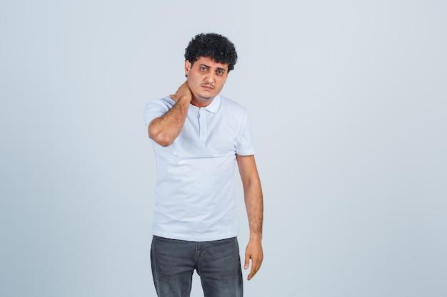 若い男は首に手を置き、白いtシャツとジーンズで首の痛みを抱えて、急いでいるように見えます。正面図。