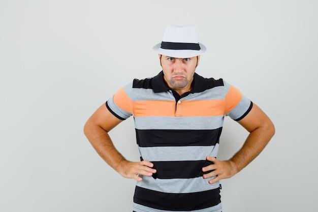 Giovane che mette le mani sulla sua vita in maglietta, cappello e che sembra arrabbiato. vista frontale.