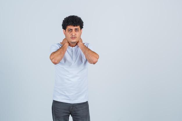 若い男は首に手を置き、白いtシャツとジーンズで首の痛みを抱えて、急いで、正面図を探しています。