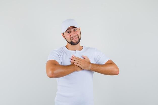 白いtシャツ、キャップで胸に手を置いて、不快に見える、正面図。