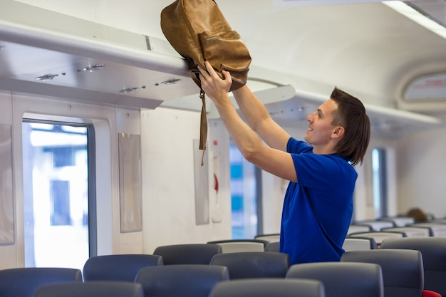 Young man putting luggage into overhead locker at airplane