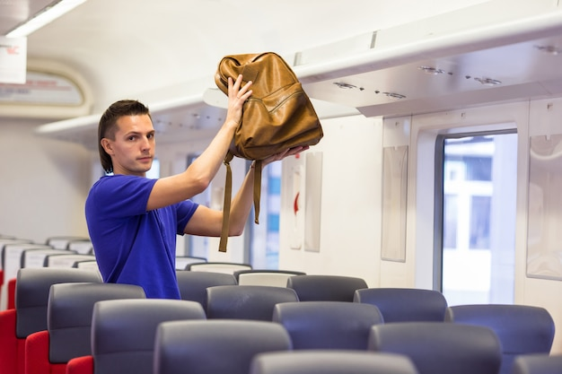 Young man putting luggage into overhead locker at train