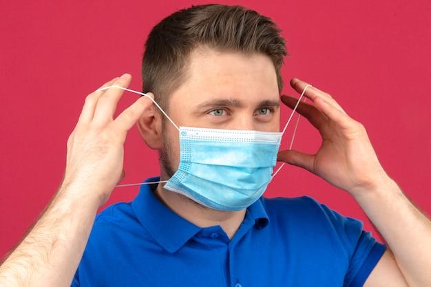 Молодой человек надевает защитную медицинскую маску на лицо над изолированной розовой стеной