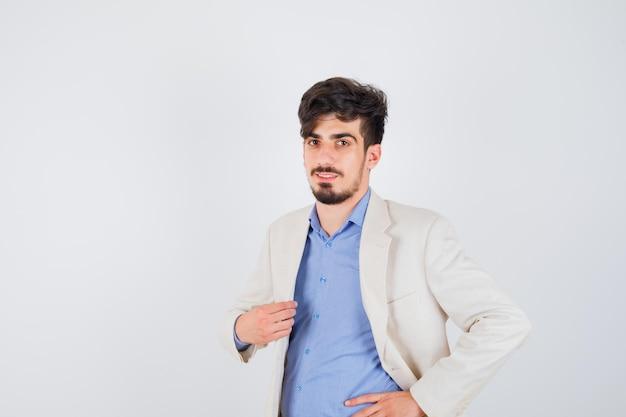한 손은 재킷에, 다른 손은 허리에 파란색 셔츠와 흰색 정장 재킷을 입고 자신감을 찾는 젊은 남자