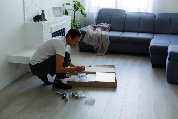 Молодой человек ставит мебель для самостоятельной сборки, когда они переезжают в ваш новый дом.