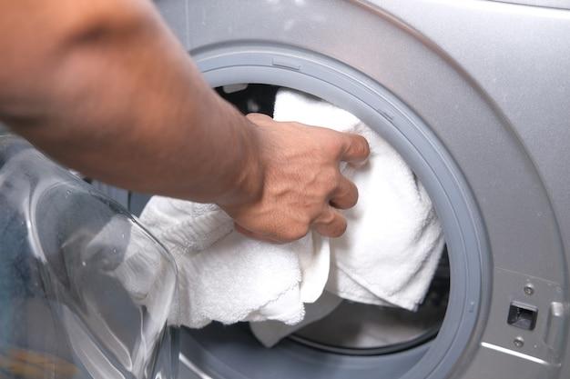 Young man putting towel into washing machine