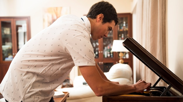 Young man putting vinyl record on player at home