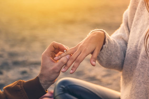 Молодой человек ставит обручальное кольцо на палец женщины