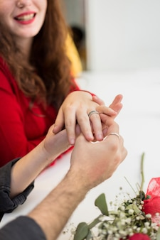Young man putting wedding ring on woman finger