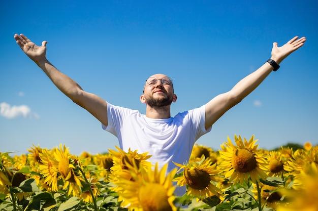 Молодой человек поднял руки к небу, показывая приветственный жест и радость солнцу на подсолнечном поле на фоне голубого неба.