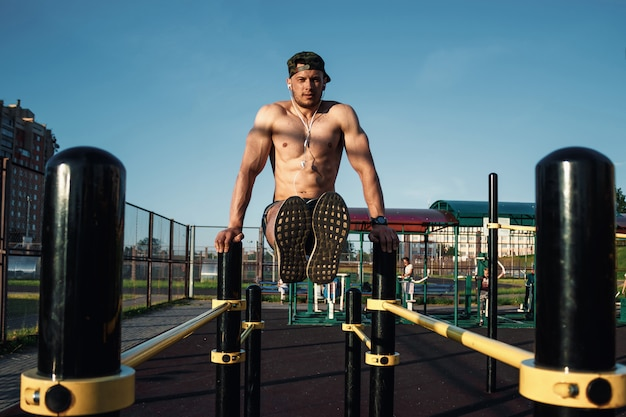 A young man raises his legs on a sports ground, an athlete, outdoor training in the city
