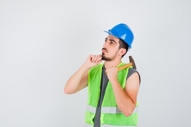 어깨 너머로 도끼를 들고 건설 유니폼을 입고 손에 턱을 기울이고 잠겨있는 찾고 젊은 남자