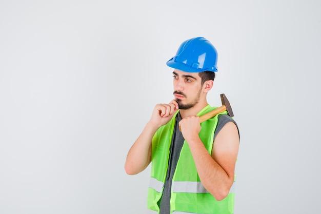 Giovane che alza l'ascia sopra la spalla e appoggia il mento a portata di mano in uniforme da costruzione e sembra pensieroso