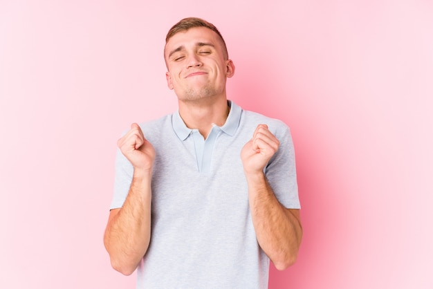 Young man raising fist, feeling happy and successful
