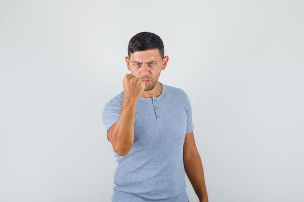 Молодой человек поднимает кулак от гнева в серой футболке