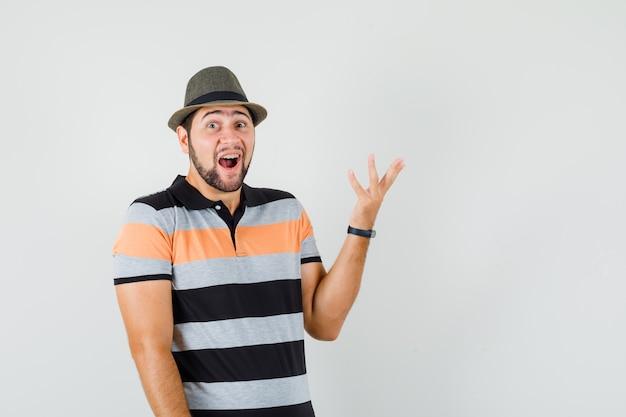 젊은 남자 t- 셔츠, 모자에 놀란 된 제스처에 손을 올리고 행복을 찾고.