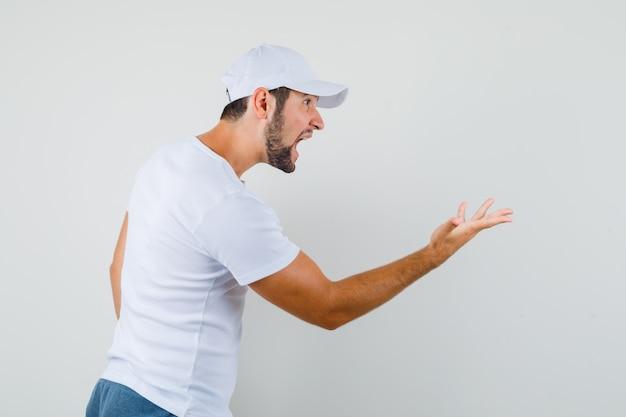 Giovane che alza la mano nel gesto interrogativo da parte mentre grida in maglietta bianca, berretto e sembra arrabbiato.