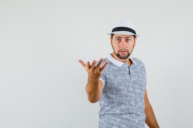 Giovane uomo alzando la mano nel gesto interrogativo in t-shirt, cappello e guardando perplesso. vista frontale.