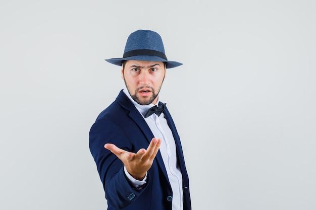 Giovane uomo alzando la mano in modo interrogativo in tuta, cappello e guardando arrabbiato, vista frontale.