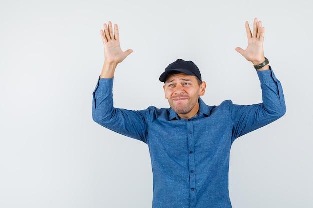 青いシャツ、キャップ、悲しそうな正面図で無力なジェスチャーで手を上げる若い男。