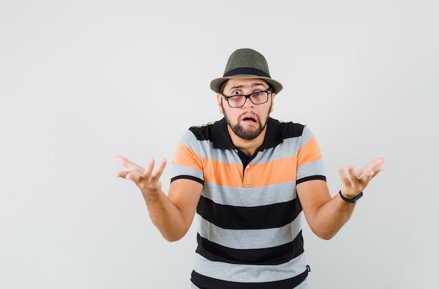 T- 셔츠, 모자 및 의아해 보이는 방식으로 심문에 손을 올리는 젊은 남자.